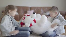 Portrait twin boy and girl sitting on the floor in living room and dont know how to share between them a big taddy bear stock video