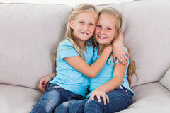 Cute twins embracing each other sitting on a couch Stock Photo