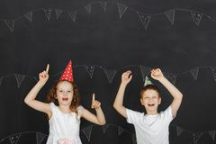 Cute twins kids with carnival hat at celebration birthday party. Stock Photography