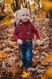 Cute twins looking at falling down autumnal leaves. Cute, little twins looking at falling down autumnal leaves royalty free stock photo