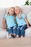 Cute twins sitting on a couch Royalty Free Stock Photos