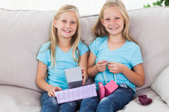 Cute twins unwrapping birthday gift sitting on a couch Royalty Free Stock Image