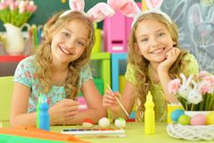 Cute twins wearing rabbit ears decorating  Easter eggs stock photo
