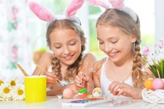 Cute twins wearing rabbit ears decorating Easter eggs stock photos