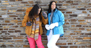 Cute twins in winter coats leaning on wall Stock Image