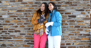 Cute twins in winter coats leaning on wall Stock Photography