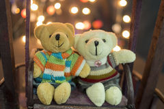 Cute two doll bears. Pair of cute teddies are sitting on wood swing with bokeh light in background. Teddies wear winter suite. Hug Royalty Free Stock Photos