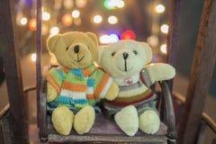 Cute two doll bears. Pair of cute teddies are sitting on wood swing with bokeh light in background. Teddies wear winter suite. Hug. Teddies. Concept of love Royalty Free Stock Photos
