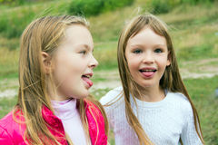Cute two playing girls put out tongues Stock Photos
