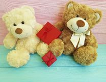 Cute two teddy bear family toy with a red box on a pink and blue wooden Royalty Free Stock Images