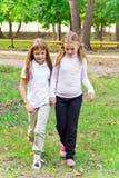 Cute two walking girls. Photo of two walking girls in summer stock image