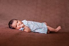 Cute two weeks old newborn baby girl lying down. Eyes open and looking around wearing a floral dress Royalty Free Stock Images