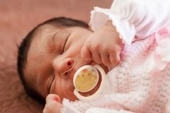 Cute two weeks old newborn baby girl with a pacifier. Close up portrait of a cute two weeks old newborn baby girl wearing soft pink knit clothes, sleeping Stock Photos