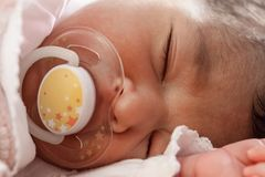 Cute two weeks old newborn baby girl with a pacifier. Close up portrait of a cute two weeks old newborn baby girl wearing soft pink knit clothes, sleeping Stock Image