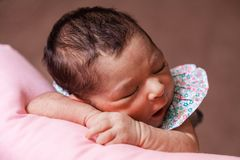 Cute two weeks old newborn baby girl sleeping peacefully. Close up portrait of a cute two weeks old newborn baby girl wearing a floral dress, sleeping peacefully Stock Images