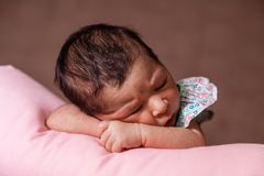 Cute two weeks old newborn baby girl sleeping peacefully. Close up portrait of a cute two weeks old newborn baby girl wearing a floral dress, sleeping peacefully Royalty Free Stock Images