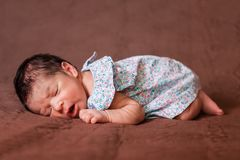 Cute two weeks old newborn baby girl sleeping peacefully. Cute two weeks old newborn baby girl wearing a floral dress, sleeping peacefully in bed in fetal Royalty Free Stock Photography