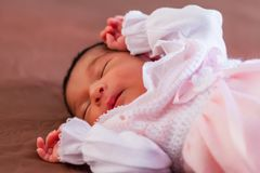Cute two weeks old newborn baby girl wearing soft pink knit clothes. Sleeping peacefully in bed royalty free stock photos
