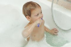 Cute two year old baby taking a bath with foam and brushing teeth.  stock image