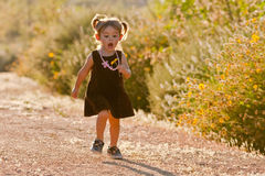 Cute two-year-old girl running outdoors royalty free stock images