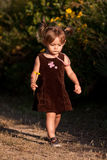 Cute two-year-old girl walking outdoors. Cute, multi-racial, 2 year old girl walks down a path.  She is daydreaming or concentrating.  She carries a little Stock Photography