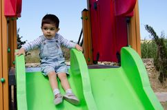 Cute two years old boy playig in the children playground outdoors on the slide stock photography