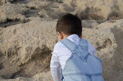 Cute two years old boy playing on the rocks in front of boat houses in malta, shoot from the back stock photography