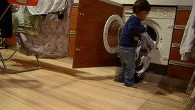 Cute two years old boy taking out washed clothes from washing machine and giving it to his mother stock video