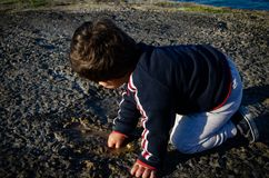 Cute two years old toddler playing with water on the stone path royalty free stock photo