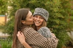 Cute two young adult women, head and shoulders shot, kiss cheek, Royalty Free Stock Images