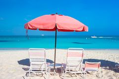 Cute umbrellas and sunbeds at tropical beach Royalty Free Stock Image