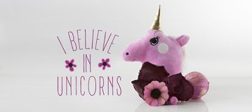 Cute Unicorn Head with text. Cute Unicorn Head with flower decoration , Sample text, `i believe in unicorns` slogan, Contemporary art, Cute unicorn head stuffed royalty free stock images