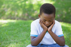 Cute upset boy pouting in the park Stock Images