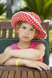 Cute upset girl wearing Panama sitting on table Stock Photo