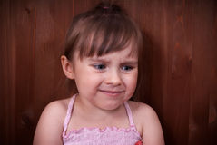 Cute upset little girl on dark wooden background Royalty Free Stock Images
