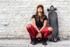 Cute urban girl with longboard sitting sitting next to a brick wall. Outdoors royalty free stock photo