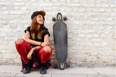 Cute urban girl with longboard sitting sitting next to a brick wall. Outdoors Royalty Free Stock Images
