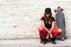 Cute urban girl with longboard sitting sitting next to a brick wall. Outdoors stock image