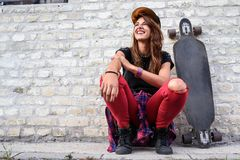 Cute urban girl with longboard sitting sitting next to a brick wall. Outdoors Stock Photo