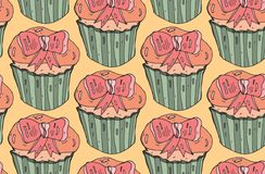 Cute  vector seamless pattern.Cupcake with pink bow on orange background.Hand painted illustration. Stock Photography