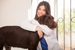 Cute veterinarian hugging a dog Stock Images