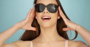 Cute vivacious woman in sunglasses Stock Photos