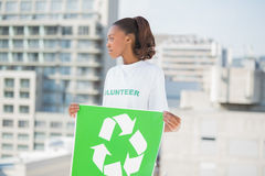 Cute volunteer woman holding recycling sign looking away Royalty Free Stock Photography