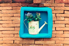 Cute watering can with flower  on the space of the center of  br. Ick wall background Royalty Free Stock Images