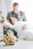 Cute wedding bouquette over wedding couple as background. Stock Image