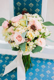 Cute wedding bouquette standing on blue chair. Stock Photos