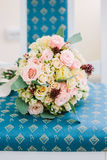 Cute wedding bouquette standing on blue chair. Stock Image