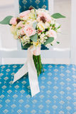 Cute wedding bouquette standing on blue chair. Stock Photo