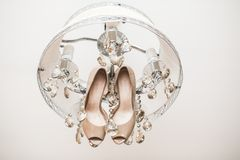 Cute wedding shoes. Beautiful wedding shoes hanging from the chandelier Royalty Free Stock Image