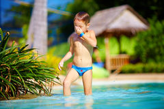 Cute wet kid, boy enjoying vacation in tropical pool Stock Photos